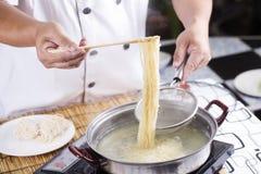 Szefa kuchni mienia colander z gotującym kluski obraz stock