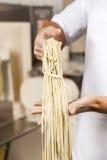 Szefa kuchni mienia spaghetti makaron Przy kuchnią Obrazy Royalty Free