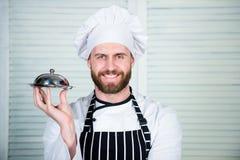 Szefa kuchni naczynie Mężczyzny fartuch i trzymamy posiłek zakrywamy z deklem Wyśmienicie posiłek prezentacja Haute kuchnia chara obraz royalty free