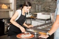 Szefa kuchni podesłania serowe polewy na pizzy bazie Obraz Royalty Free
