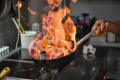 Szefa kuchni podrzucania warzyw flambe w niecce nad palnikiem obraz royalty free
