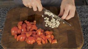 Szefa kuchni przecinania czosnek na tnącej desce z nożem zdjęcie wideo