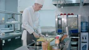 Szefa kuchni przecinania czosnek na tnącej desce z nożem i mieszać je z solą przynoszącą innym kucharzem zbiory