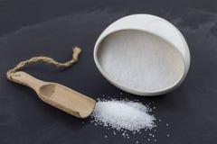 Szefa kuchni ` s solankowy ceramiczny puchar z biel solankową i drewnianą łyżką na czarnym tle obraz stock