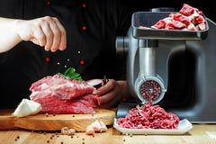 Szefa kuchni solit minced świeżego mięso na ciemnym tle obrazy stock