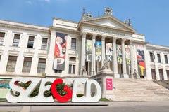SZEGED UNGERN - JULI 21, 2017: Huvudbyggnad av Mora Ferenc Museum slutligen av eftermiddagen, med den Szeged logoen framme Royaltyfri Foto