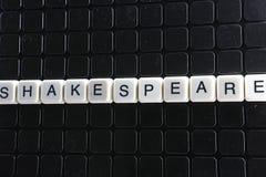 Szekspir teksta słowa tytułowego podpisu etykietki pokrywy tła tło Abecadło listu zabawki bloki na czarnym odbijającym tle Wh Zdjęcia Stock