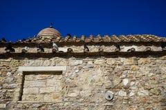 Szene der alten klassischen kleiner Kirche im Erdtonnaturstein mit Tauben auf Terrakottadachplatte mit klarem Hintergrund des bla Lizenzfreie Stockfotos