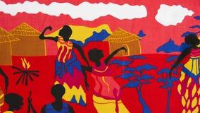 Szene des traditionellen Lebens auf einem Stück eines roten Baumwollgewebees stockbilder