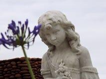 Szene in einem Kirchhof: Statue eines Mädchens, das einen Blumenstrauß hält lizenzfreies stockfoto