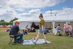 Szene im Freien eines Live-Musik-Festivals, das Gruppen Familien außerhalb eines großen Festzelts in der Sommerzeit zeigt stockfotografie