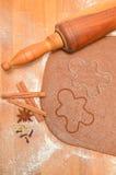 Szene stellt gerollten Mannplätzchenschneider des Teigs, der Gewürze, des braunen Zuckers, des Eies und des Lebkuchens dar Szene  Stockbild