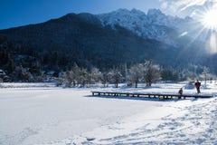 Szenische Ansicht über wunderbares gefrorenes See jasna mit Steg in den julianischen Alpen im blauen Himmel, Kranjska Gora, Slowe Lizenzfreie Stockfotos