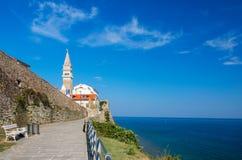 Szenische Ansicht der Küstenlinie von adriatischem Meer mit Gasse entlang alten Stadtmauern und Kathedrale Piran auf Hintergrund, stockfoto