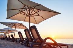 Szenische Ansicht des sandigen Strandes auf dem Strand mit Sonnenbetten und Regenschirme öffnen sich gegen das Meer und die Berge Lizenzfreies Stockbild