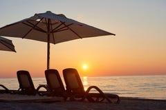 Szenische Ansicht des sandigen Strandes auf dem Strand mit Sonnenbetten und Regenschirme öffnen sich gegen das Meer und die Berge Lizenzfreie Stockfotos