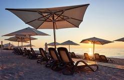 Szenische Ansicht des sandigen Strandes auf dem Strand mit Sonnenbetten und Regenschirme öffnen sich gegen das Meer und die Berge Stockbild