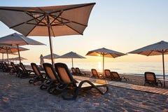 Szenische Ansicht des sandigen Strandes auf dem Strand mit Sonnenbetten und Regenschirme öffnen sich gegen das Meer und die Berge Lizenzfreie Stockbilder