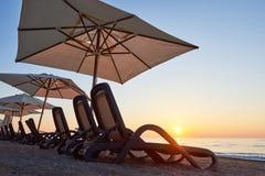 Szenische Ansicht des sandigen Strandes auf dem Strand mit Sonnenbetten und Regenschirme öffnen sich gegen das Meer und die Berge Lizenzfreie Stockfotografie