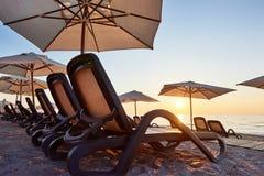 Szenische Ansicht des sandigen Strandes auf dem Strand mit Sonnenbetten und Regenschirme öffnen sich gegen das Meer und die Berge Stockfotos
