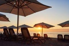 Szenische Ansicht des sandigen Strandes auf dem Strand mit Sonnenbetten und Regenschirme öffnen sich gegen das Meer und die Berge Stockfotografie