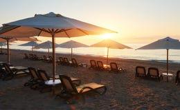 Szenische Ansicht des sandigen Strandes auf dem Strand mit Sonnenbetten und Regenschirme öffnen sich gegen das Meer und die Berge Stockbilder
