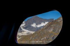 Szenische Ansicht durch Schiffshafenloch/Fenster von Schnee bedeckten Bergen lizenzfreies stockfoto