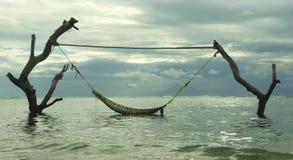 Szenische Ansicht einer Einladung und überraschende Einrichtung der verlockenden Seehängematte auf Baumstämmen am Tropeninselstra stockfoto