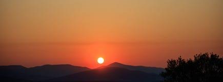 Szenische Ansicht eines orange Sonnenuntergangs über den Bergen Lizenzfreies Stockbild