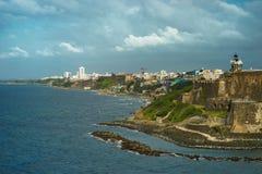 Szenische Ansicht historischer bunter Puerto- Ricostadt im Abstand mit Fort im Vordergrund Lizenzfreies Stockbild
