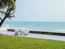 Szenische Ansicht-Kombination vierteilig, die Gras-Boden, weiße Steintabelle im Decking, blaues Meer und klarer Himmel als Copysp Lizenzfreie Stockbilder