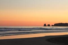 Szenische Ansicht kurz vor Sonnenaufgang von Schattenbild deux jumeaux im bunten Sommerhimmel auf einem sandigen Strand Lizenzfreies Stockbild