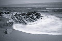 Szenische atlantische Küstenlinie mit Wellen in der Bewegung um Felsen auf sandigem Strand in der langen Belichtung, bidart, bask Stockfotos