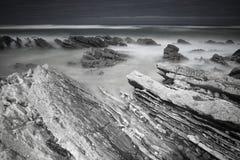 Szenische atlantische Küstenlinie mit Wellen in der Bewegung um Felsen auf sandigem Strand in der langen Belichtung, bidart, bask Lizenzfreies Stockfoto