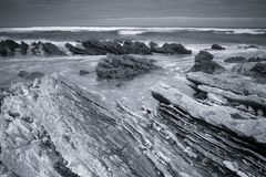Szenische atlantische Küstenlinie mit Wellen in der Bewegung um Felsen auf sandigem Strand in der langen Belichtung, bidart, bask Stockfotografie