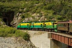 Szenische Eisenbahn auf weißem Durchlauf und Yukon verlegen beim Eintragen des Bottichs Stockfoto