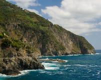 Szenische Klippen mit Dorf und grün-blauem Meer Stockbilder