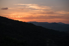 Szenische Landschaft der Sonneneinstellung hinter den Bergen Lizenzfreies Stockbild