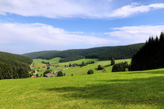 Szenische Landschaftslandschaft im Schwarzwald: grünes Sommergebirgstal mit Wäldern, Feldern und alten Häusern herein Stockfotos