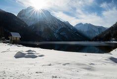 Szenischer Gebirgspass lake Lago Del Predil mit Haus in der Winterlandschaft mit blauem Himmel des Sonnenlichts, Italien Stockfotos