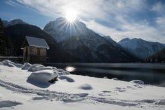 Szenischer Gebirgspass lake Lago Del Predil mit Haus in der Winterlandschaft mit blauem Himmel des Sonnenlichts, Italien Lizenzfreies Stockfoto