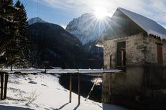 Szenischer Gebirgspass lake Lago Del Predil mit Haus in der Winterlandschaft mit blauem Himmel des Sonnenlichts, Italien Lizenzfreie Stockfotografie