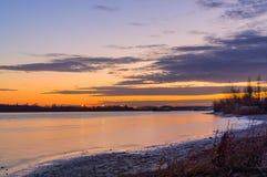 Szenischer Himmel über dem Fluss zur Sonnenuntergangzeit Ansicht vom Ufer Lizenzfreie Stockfotos