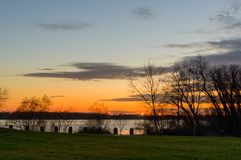 Szenischer Himmel über dem Fluss zur Sonnenuntergangzeit Ansicht vom Ufer Stockbilder