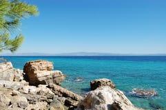 Szenischer Meerblick mit Steinküsten- und Türkismeer in Griechenland lizenzfreies stockfoto