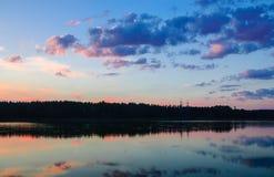Szenischer Seeblick mit Wald bei Sonnenuntergang stockfotos