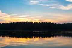 Szenischer Seeblick mit Wald am sunsetScenic Seeblick mit Wald bei Sonnenuntergang bei Sonnenaufgang lizenzfreies stockbild