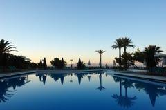 Szenischer Sonnenuntergang durch das Meer, das blaue Pool und die Palmen in einem Hotel herein stockfotografie
