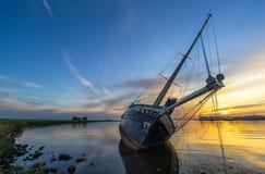 Szenischer Sonnenuntergang an einem angeschwemmten Segelboot nahe Lemmer, die Niederlande Stockbild