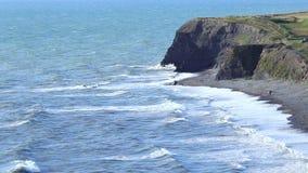 Szenisches felsiges Ufer von Waliser-Küstenlinie am hellen sonnigen Tag stock footage